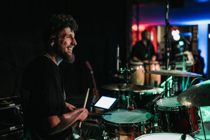 Schlagzeuger Charly Beat sitzt am Drumset und lacht. Man sieht ein Ipad und ein Conga im Hintergrund