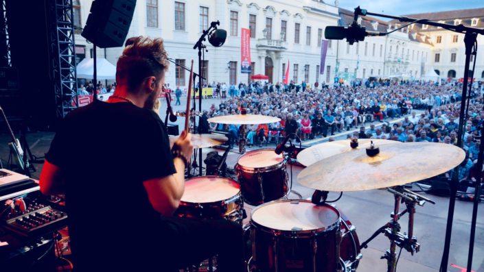 Charly Beat spielt Schlagzeug. Blick von hinten von der Bühne in Ludwigsburg